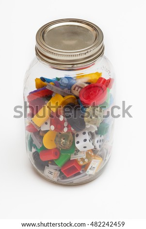 An old jar filled with a variety of old game pieces