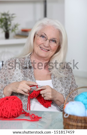 An old lady knitting. - stock photo