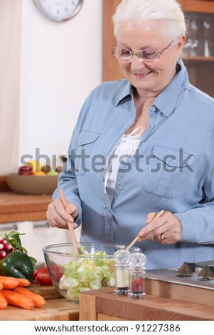 An old lady making a salad. - stock photo