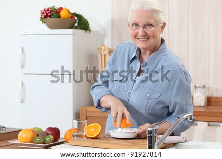 An old lady pressing oranges. - stock photo