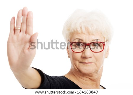 An old lady showing stop sign by hand. Isolated on white.  - stock photo