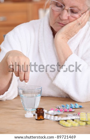 An old lady taking pills. - stock photo