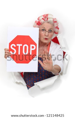 An old lady with a stop sign. - stock photo