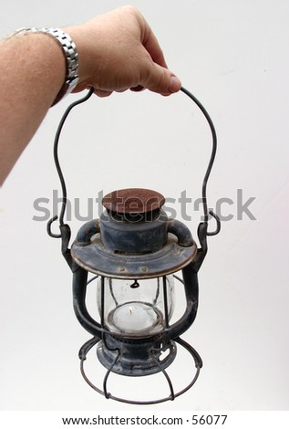 An Old Lantern With Some Rust And A Lit Candel Inside Being Held By Real