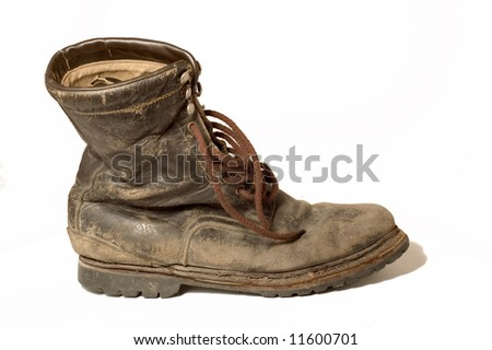 An old leather boot, well worn, dirty, and isolated on white