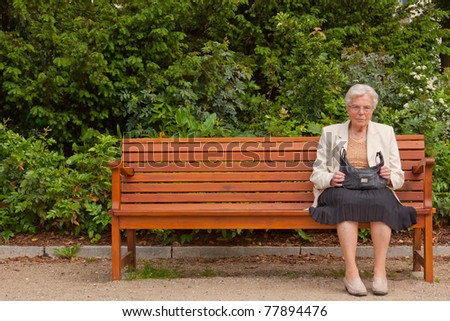 An old lonely woman is sitting on a bench in a park - stock photo