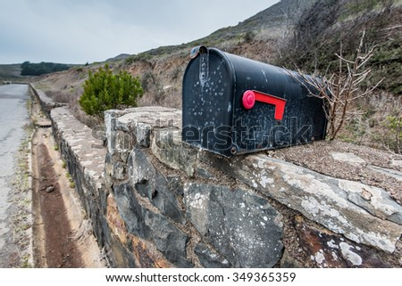 An old mailbox sits on a stone slab wall with a tree branch behind it - stock photo