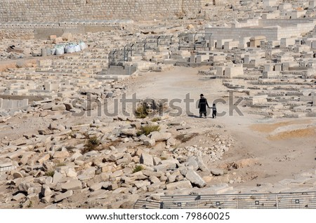 An old man and his grandson are walking down the cemetery in the Kidron Valley in Jerusalem, Israel - stock photo
