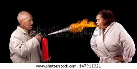 An old man attempts to extinguish the flames that emanate from the mouth of a younger woman. - stock photo