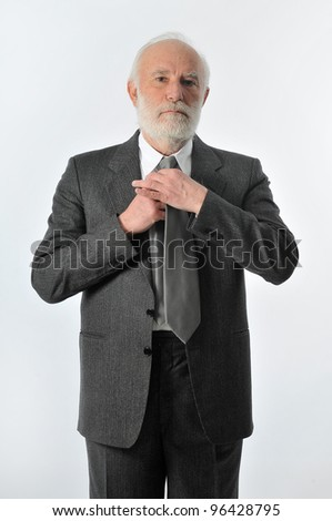 an old man fixes his tie - stock photo