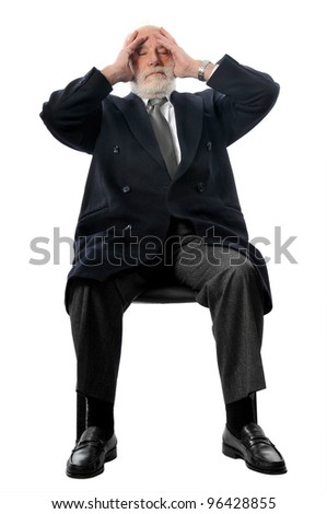 an old man holds his head - stock photo