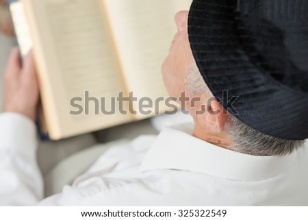 An old man in a traditional black hat reading a book. Selective focus