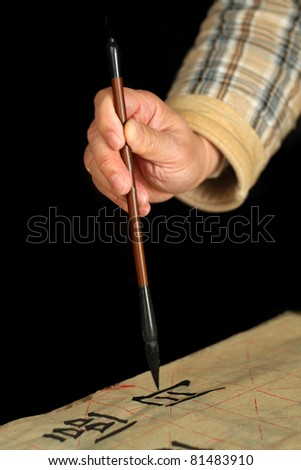 An old man is practicing calligraphy using a brush pen in his leisure time