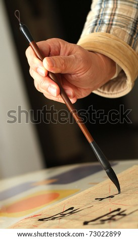An old man is practicing callingraphy using a brush pen in his leisure time - stock photo