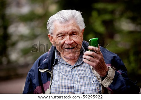 An old man laughing and smiling with a cell phone. - stock photo