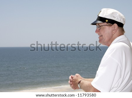 An old man looking out at the sea. - stock photo