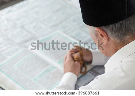 An old man reading Koran. Selective focus