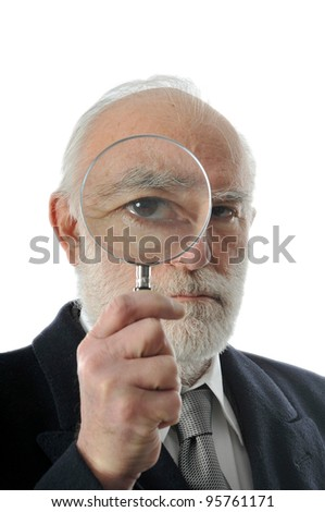 an old man sees through in magnifying lens - stock photo