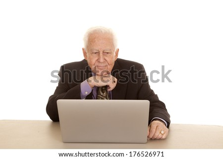An old man sitting at a computer wearing a suit and tie.