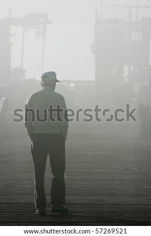 An old man walking into the fog