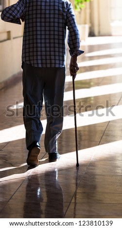 an old man with a cane on the sidewalk - stock photo
