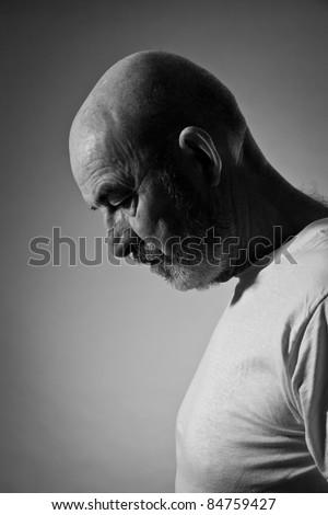 An old man with a grey beard in sorrow - stock photo