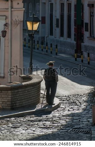 An old man with a wooden stick and a laurel wreath around his head, walking through the old part of the city - stock photo