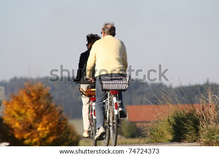 An old married couple ride with bicycle - stock photo
