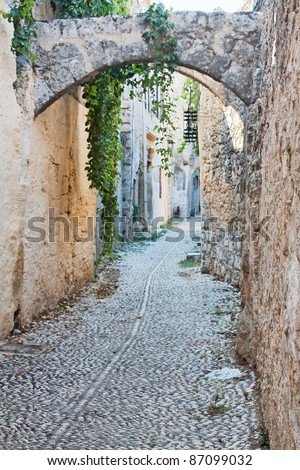 An old medieval cobblestone alley in Rhodes Old Town (a UNESCO World Heritage Site), Greece, with arches and stone facades. - stock photo