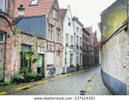 An old medieval empty side street of Bruges, Belgium, with a bike parked at one side - stock photo