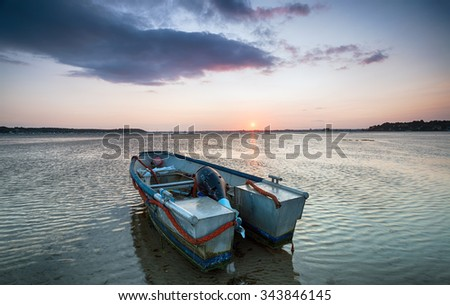 An old metal boat at sunset at Sandbanks in Poole Harbour in Dorset - stock photo