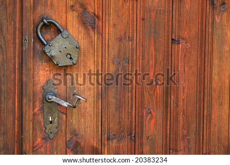 An old metal padlock on a heavy wooden gate - stock photo