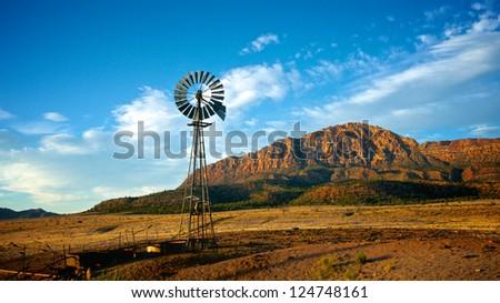 An old metal windmill lies beneath a Utah mountain. - stock photo