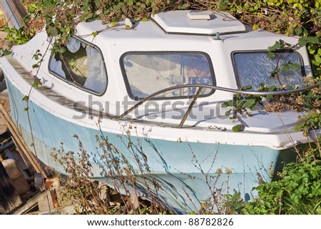 An old motorboat abandoned ashore in undergrowth - stock photo
