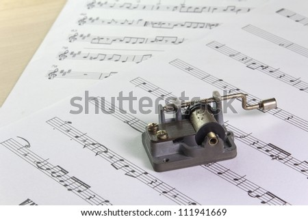 an old music box with note sheets on a desk - stock photo