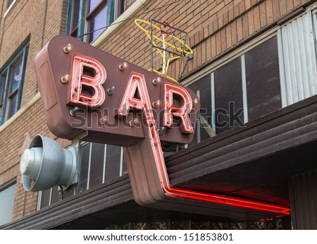 An old neon sign for a bar featuring a martini glass. - stock photo