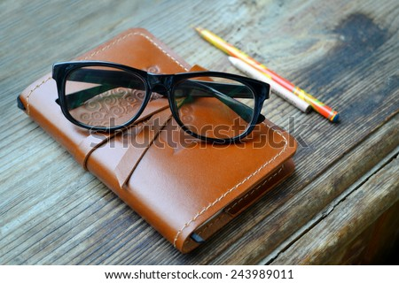An old notebook in leather cover with pencils and glasses on wooden table - stock photo