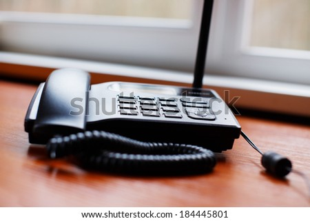 An old office phone on the table - stock photo
