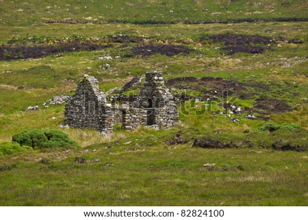 An old one roomed, stone built cottage stands roofless and ruined in the middle of a peat bog in Donegal, Ireland, an abandoned relic acting as a historical reminder of times of poverty or famine. - stock photo