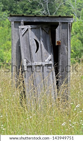 An old outhouse with door falling off surrounded by weeds. - stock photo