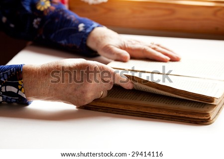 An old pair of hands holding the pages in a book, reading. - stock photo