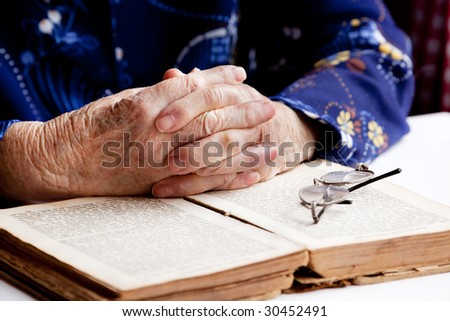 An old pair of hands in prayer on a book - stock photo
