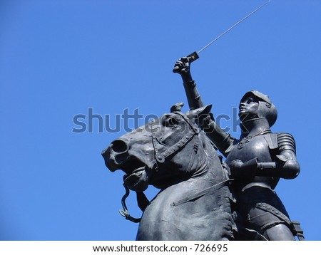 An old park statue from the late 1800's holds  up a sword up in an apparent show of victory.  The statue depicts a female