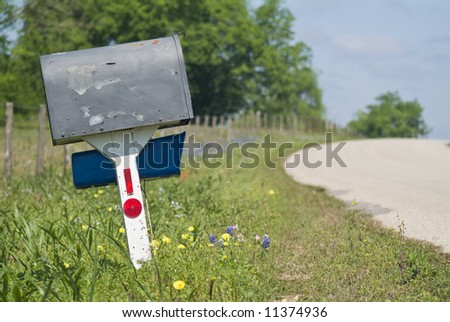 An old peeling mailbox by the side of a wildflower edged country road. - stock photo