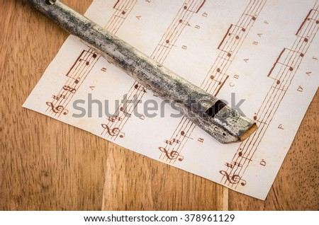 An old Penny Whistle and sheet music on an oak desk. - stock photo