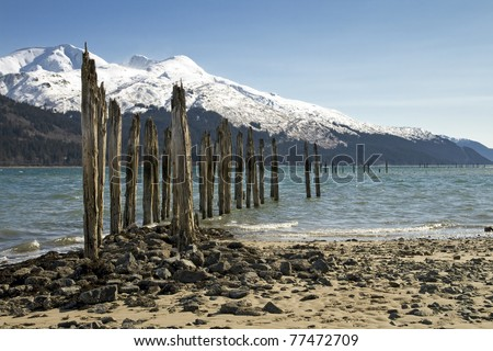 An old pier at a mine in Juneau, Alaska against a mountain backdrop. - stock photo