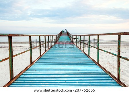 an old pier on the sea during the day, the bright sun and relaxation alone. You can be alone with yourself and do yoga or meditate. - stock photo
