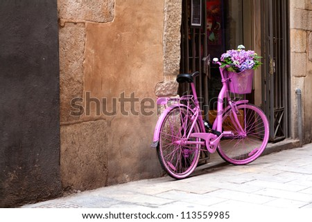 an old pink bike standing on the street - stock photo