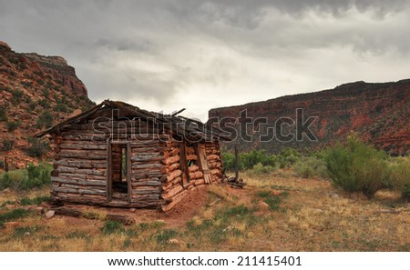 An old pioneer cabin sits in nestled against the red rock cliffs of Western Colorado. - stock photo