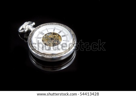 An old pocket watch on black background with reflection - stock photo